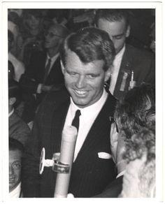 American politician, New York Senator Robert F. Kennedy (1925-1968) standing amongst a crowd of people