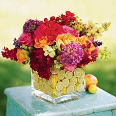A playful mosaic of fresh citrus slices makes inexpensive glass flower vases look as refreshing as lemonade.  Start by nesting a small vase inside a large one (we used 4- and 6-inch square vases). Slip lemon and/or lime slices between the two; fill the gap with water. We completed our centerpiece with an arrangement of punchy peonies, roses, salvias, alliums, geraniums and orchids.