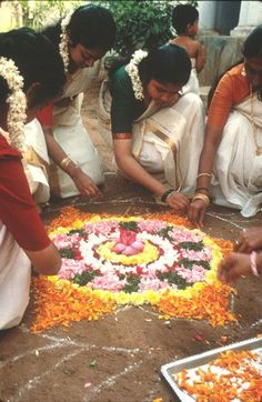 Girls making Rangoli with flowers on the occasion of Onam, The New Year celebration in Kerala, India