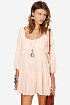 The sweetest apricot babydoll dress featuring a flowy skirt and strappy detailing at back. Slip o...