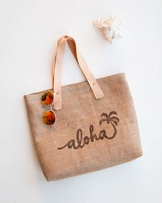 Natural Jute Beach Bag // Burlap Beach Tote  A classic jute bag designed to spread good vibes and aloha wherever it goes.  It features an aloha and palm tree stamped on one side and is plain burlap on the other. I carve my own stamps with my original designs and block print them using water based screen printing ink. This tote has some really special details, like blush leather handles with cute little fringes on the ends. The bag is fully lined in a coordinating peachy pink batik p...