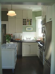 white cabinets, dark floor, dark counters, island with marble top, stainless appliances.