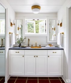 The crisp white master bath has a marine-style ceiling fixture from Circa Lighting and sconces by Thomas O'Brien for Visual Comfort.