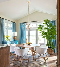 The dining room stays casual with furniture from Crate and Barrel: a round, modern table and chairs made from easy-care synthetic rattan. Lights and window shades can be programmed so that it looks like you're home or could come home anytime.