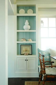 Built-in cabinets with turquoise blue beadboard backsplash and beachy accents.