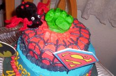 great grandson's super hero 4th. birthday cake. The Hulk's fist is made with green tinted white chocolate modeling clay. Spider was made of pompom's and pipecleaners signs are poster board.