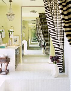 Palazzo Curtains - In this master bathroom, designer Michael Berman hangs striped palazzo curtains in Victoria Hagan fabric from Holly Hunt on either side of a sunken tub