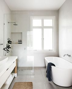 """Light and air take pride of place here, providing the perfect place for precious me-time. """"The approach with this family bathroom was to create a light, modern space,"""" says Fiona Lynch, who created the design for the bathroom. """"The freestanding vanity bench with timber dowel leg detail and mesh drawer fronts is subtle, but textural. Neutral tiling sits neatly as a light backdrop."""" Corian **benchtop** in Glacier White from [CASF](http://casf.com.au/