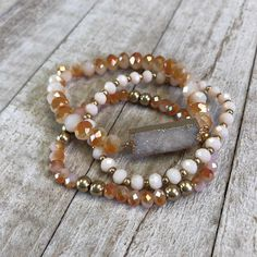 Feast your eyes upon one of our DRUZY BRACELETS! A #druzy is the glittering effect of tiny #crystals over top a colorful mineral. This trio of peach #beads with a beautify ivory druzy stone is sure to dazzle! #accessorizeyouroutfit #bracelet