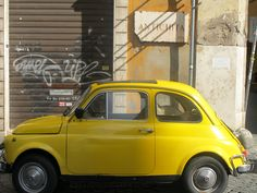 "Yellow vintage Fiat 500, parked under the ""Antiques"" sign on the streets of Rome, February 2013."