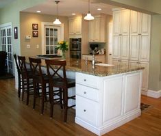 Granite counters, island with sink and cooktop, double oven, hardwood floors.