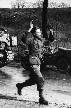 A German soldier runs towards Allied forces in surrender. Lemgo, 1945. William Vandivert