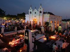 Photo: People visiting graves in candle-lit cemetery
