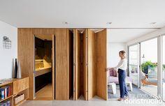No apartamento paulistano de 58 m², o painel de madeira não é apenas parte das soluções em nome da amplitude, mas sim protagonista. Ele surge como elemento versátil e contínuo separando e ligando ambientes, organizando e setorizando usos na casa