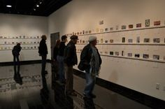 Attendees observe postcard exhibit entries in the Minnaert Center for the Arts. Photo by James Egaran