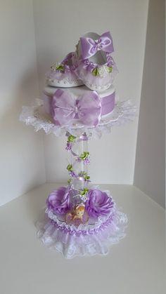 Centro de mesa para baby shower. Base de plástico decoradas con flores de raso hechas a mano, estilo kanzashi, encajes y un pequeño bebé. La base de la parte superior de la pieza central está decorada con foami, cinta de raso y encaje. Y para completar la decoración, en la parte superior, un zapatos de bebé hechos a mano de foami, adornado con cinta y perlas. La pieza central mide 19 de alto por 9 de ancho aproximadamente.  El listado es para un centro de mesa de lavanda, puede elegir entre…