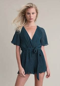 Green romper in pleated fabric with shimmer accents, crossover v-neckline, elasticated waist, soft ruffled sleeves and self tie fastening. Partially lined.