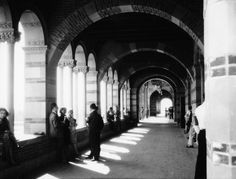(1929) - View of Royce Hall, at the time that the UCLA Westwood campus opened in 1929. Looking down the outside hallway of Royce Hall. Small groups of students are seen standing, while others are seated on ledges beneath the arches.