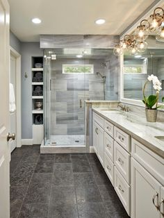 This beautiful master bathroom pulls elements from traditional and modern design styles. Recessed lighting paired with modern globe sconces -- and a small window over the shower -- ensures an always-bright space. Lena white marble, quartzite counters and limestone floors make the room feel rich and inviting.