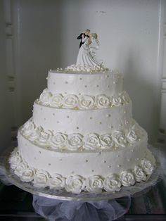 white wedding cake with roses of whipped cream