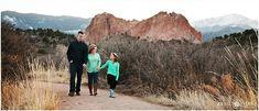 A family wearing shades of turquoise and black sit on a fence together in front of the dramatic red rock formations at Garden of the Gods in Colorado Springs during their family photo session in the spring. - April O'Hare Photography http://www.apriloharephotography.com #ColoradoSprings #ColoradoSpringsFamilyPhotos #GardenoftheGods #GardenoftheGodsFamilyPhotos #Colorado #ColoradoFamilyPhotos