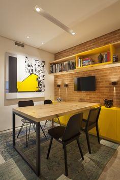 A sala de jantar pode ter toques curingas: O amarelo e a parede em tijolos, dão um ar moderno e ao mesmo tempo rústico, a TV torna o ambiente acolhedor.