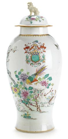 A LARGE FAMILLE ROSE ARMORIAL VASE AND COVER  CIRCA 1750  Of baluster form, enamelled with the arms of Tolson above a brightly colored pheasant perched among weathered rocks, magnolia, lilies and large peony blooms, the rims with a gilt spearhead band, the finial as a Buddhistic lion  21½ in. (54.6 cm.) high (2)
