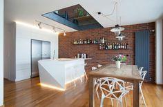 Barbara Bencova – B2 architecture.    Hlavní obytný prostor se nachází ve druhém patře bytu, prosklennou podlahou je propojený i do nejvyššího patra, kam prochází i cihlový obklad stěny. K němu a rustikálnímu stolu a svítidlům kontrastuje moderní bílá kuchyně. Design: www.b2architecture.eu