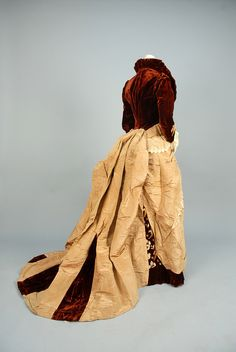 """MOIRE SILK and VELVET GOWN with EMBROIDERY, c. 1878. Boned garnet velvet bodice having wired collar and self buttons, polychrome embroidered floral and lace trim, trained bustle skirt of tan moire silk with embroidered velvet front panel and lace swags. Petersham label """"Mme. Dellac, New York"""""""