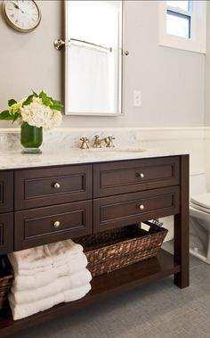 Furniture Style Bathroom Vanity with dark stain and Carrara marble countertop designed by Rockwood Cabinetry.