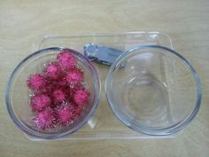 Transferring sparkle pom poms with a strawberry huller.