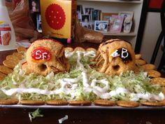 Superbowl Party food.  Cheeseball helmets on a bed of buffalo chicken dip.