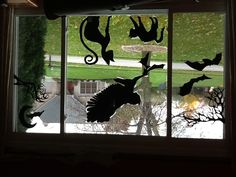Halloween Silhouettes for Windows - For Halloween 2012, the front window was a display for cut-outs I made from black poster paper. It was all free-hand sketches from combinations of pictures and photos I wanted to incorporate. 1. Branches and two bats in the left panel. 2. Branches, moon, and bat in the right panel. 3. In the middle, my owl is snatching its torn-up bat-prey. Then there are my black cats: one hissing and one arching.
