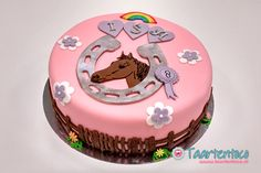 Roze taart met bovenop een uit fondant gesneden paard.