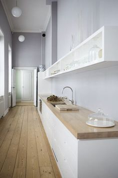 cuina blanca minimal amb encimera de fusta.