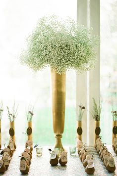 A tall, gold vase filled with baby's breath hovers over 120 pears with hand-calligraphed name tags.
