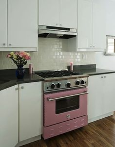 a pop of pink in a black and white kitchen
