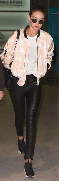 Who made  Gigi Hadid's round sunglasses, tan jacket, black sneakers, leather pants, and handbag?