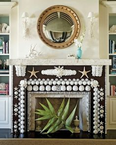 Statement made! We love the beach! Great decorating with shells.    Fireplace, gold mirror, starfish, white shells, bookshelves, bookcases, books, island beach tropical nautical home decor