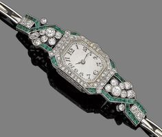 An emerald and diamond cocktail watch, circa 1930  The hexagonal dial with Arabic numerals, within a single-cut diamond and calibré-cut emerald bezel, to openwork tapering shoulders set with similarly-cut emeralds, single and old brilliant-cut diamonds in collet-settings, to an expandable brick-link bracelet, diamonds approx. 1.65cts total, length 15.7cm