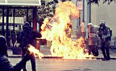 Greek policeman is hit by a Molotov incendiary device .