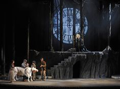 "Into the Woods. Theatre du Chatelet, Paris. Set design by Alex Eales.  Dominent design element is line, especially the contrast of the vertical lines created by the trees agains the large circular image created by the ""moon clock"" up center.  This is a powerful composition, elevating the witch above the principle players and suspending the clock behind her."