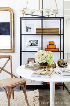 Total Makeover: Inside Our Co-Founder Katherine Power's Elegant New Office // round white tulip table, Ikea bookcases, brass mirror, brass lantern, bentwood chair, sisal rug, brass skull