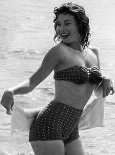 AVA GARDNER being playful on the beach. Wearing a cute two piece bathing suit ca 1950's.