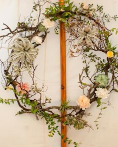This decorative wreath combined succulents, branches, air plants, vines, and…