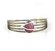 Five Strand Cuff with Organic Red Sapphire. The Bondage Collection, Five strand cuff of blackened sterling silver and sterling silver straps and rivets with an organic shaped red sapphire (9ctw).