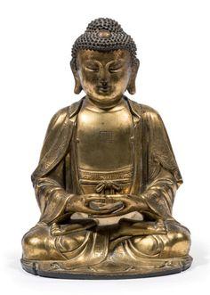 CHINE - XVIIe siècle Statuette de bouddha en bronze doré assis en padmasana les mains en dhyana mudra, le buste incisé d'une svastika, le visage serein, les yeux entrouverts, portant une robe monastique à décor de fleurs de lotus. H. 17,5 cm. La svastika sur le torse de bouddha représente le sceau du coeur de bouddha, symbolisant la totalité de l'esprit de bouddha.