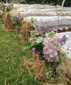 Country wedding with hay bale seating & jam jar flowers on shepherds crooks