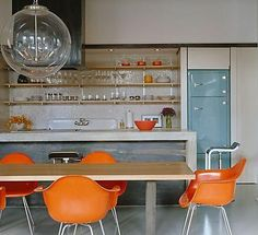 Colorful orange molded plastic Eames dining chairs add a jolt of retro flair to this otherwise neutral modern and sleek gray and blonde wood kitchen.