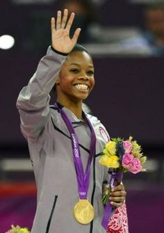 Gabrielle Douglas (USA) waves to the crowd after receiving her gold medal for winning the women's individual all-around final during the 2012 London Olympic Games at North Greenwich Arena.